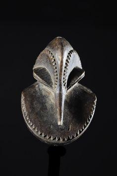 """Les masques miniatures, aussi appelés """"masques passeport"""" sont sculptés pour accueillir les esprits ancestraux, à l'instar des grands masques. Ces masques Hemba dans leur taille normale représenteraient un chimpanzée et auraient été utilisés par les sociétés secrètes Bugado et Bambudye lors de cérémonies funéraires. Les danseurs, vêtus d'un costume de fourrure, portaient une perruque blanche et noire évoquant le pelage du singecolobus."""