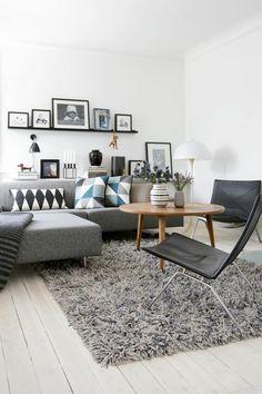 sofa stoff graues sofa teppich dekokissen geometrische muster wandbilder bilderleisten