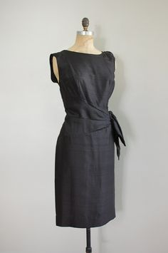 vintage 1950s, early 1960s black raw silk cocktail dresss, sleeveless with gathered silk applique at one shoulder and asymmetrical draped and swag waist. bust darts and straight skirt. metal back zipper. ________________________    fits like: large  bust: 38-40  waist: 32  hip: 41  slength: 41  brand/maker: handmade  condition: excellent    ✩ ✩ to shop more vintage dresses ✩ ✩ http://www.etsy.com/shop/DearGoldenVintage?section_id=5986725