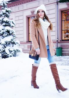 chambray shirt; cream cable knit sweater; light wash skinny jeans; tan leather riding boots; camel winter coat; cream scarf; cream beanie