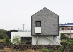 Panoramic windows puncture the grey brick walls of this guest house on Jeju Island