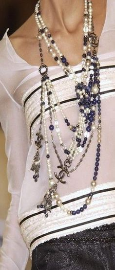 Chanel multi-strand black and white pearl necklaces accentuate the blouse greatly