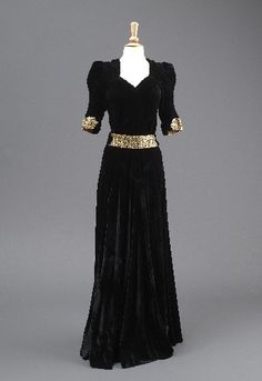 1930-32 Madame Clapham; Black velvet evening dress, with gold lamé and plastic gemstone decoration on cuffs, high front fastened by four buttons, low v-neck on back, elbow length sleeves, gathered panel at back, cut on bias, matching belt, full length.