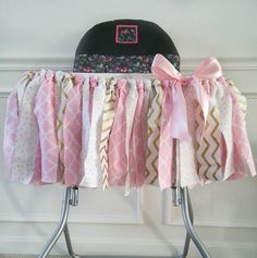 Our high chair tutu is super cute for any little one's birthday party! Made with 3 coordinating fabrics in pink, gold, and white fabrics.  It's 35 inches long and fits standard high chair trays.   All of our high chair tutus come with hook and loop fasteners attached so you can easily attach it to your high chair
