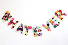 this is pretty pompom puffy cute. letter garland, balls style.