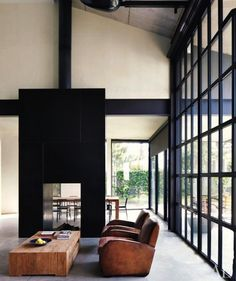 Black fireplace and wall of windows.  Great mixed with the brown leather of the chairs and chunky wooden table.