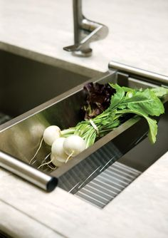 An undermount single-bowl stainless steel sink by Julien features both a removable colander and a bottom grid (ideal for drying fine glasses).