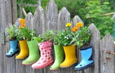 Cute rain boot planter. Each boot should have a drainage hole drilled to help excess water escape after watering. To hang boots on a fence you can use cup hooks.  Boots grouped at the entry to a mudroom would be an interesting alternative to a fence