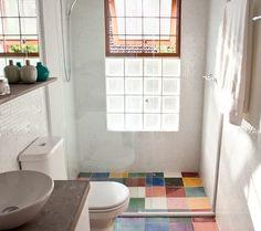 o banheiro tem base branca, mas divertido mosaico de cores dos ladrilhos hidráulicos da dalle Piagge (Foto: Lufe Gomes)