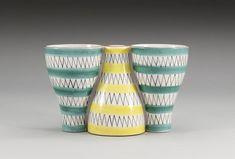 Tre konande kopplade vaser med zigzag-mönster i svart samt randdekor i turkos och gult. Höjd 12, längd 20 cm