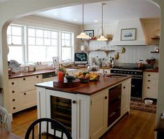 Gorgeous English-style kitchen with cherry countertops, creamy white cabients, and custom hood surround