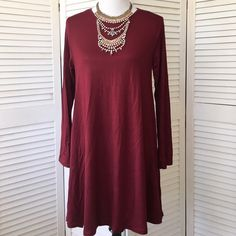 Long sleeve burgundy stretch knit swing dress So cute and flirty! Lightweight burgundy knit. Perfect amount of stretch. Scoop neck, long sleeves. No size tag, but in my opinion, will fit a small or medium. NWT; never even tried on. Buzy Collection Dresses Long Sleeve