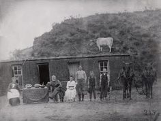 American pioneer family in front of their home--a little reminder that it really could be much worse