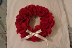 Christmas wreath made from circles of felt pinned into polystyrene hoop and decorated with ribbon