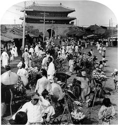 남대문 안쪽의 풍경. 장이라도 섰는지 많은 사람들이 배추 같은 채소 지게를 내려 놓고 팔고 있다.