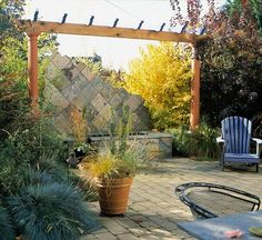Add extra zing to your water feature by framing it with an arbor or pergola. Slate tiles covering the vertical surfaces of the fountain angle down from one corner, lending the space an informal feel. A large shrub in glorious fall color balances the arbor and fountain./