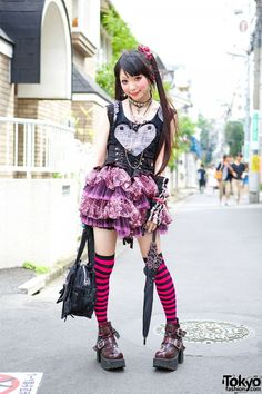 Ringo, 18 year old, student. She is wearing a heart h.NAOTO corset over a black t-shirt, with an animal print tutu from Algonquins. She is carrying both a corset-style handbag and a lace backpack with wings from h.NAOTO. Her buckle, cutouts and spikes ankle boots are from Yosuke USA, worn with striped over the knee socks.She accessorized with hair bows, spiderweb earrings, chokers, necklaces and different rings, including a Vivienne Westwood armor ring. Ringo's favorite fashion brand is…