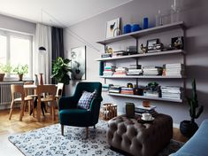 Living room with grey walls and same grey painted wall shelves, cobalt blue accents, dark turquoise arm chair, small dining area with modern lamp. Photo by Jonas Ingerstedt Photography.