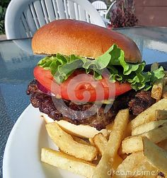 A juicy hamburger, garnished with tomato, lettuce and onion, served with fries outside on the patio.
