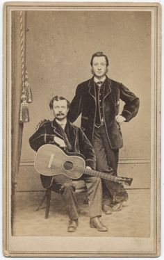 Two men, one holding guitar