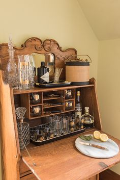 The at home bar from an antique drop front secretary desk styled with vintage barware.  Hendricks and Campari, this may be a the start of a Negroni cocktail station.    Shop for vintage kitchenware at shopvintagegrace.com
