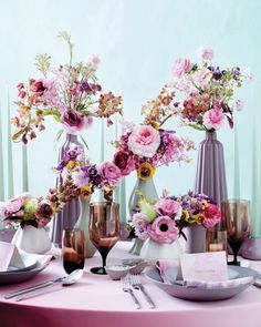 """Bohemian Centerpiece ~ Vivid pansies, ranunculus, and orchids look like a kaleidoscopic image gone 3-D. """"To bring the flowers forward, I put them in neutral vases that fade into the background,"""" says Robbins. He used Ikea """"Ovantad"""" vases in gray and white and Eva Zeisel vases in gray-green."""