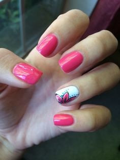 Pink nails with a white ring finger that has a flower design on it.