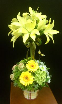 This is a topiary with yellow lillies, gerbera daisies, roses, and hypericum. Love the butterfly touch. Apologies for the bad quality; many of our floral arrangement pictures are taken with a phone.