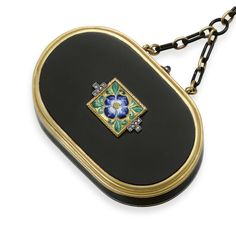 AN ART DECO ENAMEL, DIAMOND AND GOLD VANITY CASE, BY CARTIER   Of oval outline, the black enamel case with 18k gold trim, centering upon a gold plaque with a blue, white and yellow enamel flower extending green enamel leaves, with rose-cut diamond detail, the cabochon sapphire pushpiece opening to reveal a fitted mirror and a powder compartment, suspended by a black enamel and gold link chain, mounted in 18k gold, circa 1925, with French assay marks and maker's mark  Signed Cartier