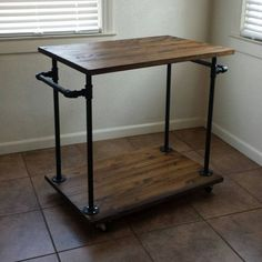 Industrial Kitchen Cart made with sturdy pipe legs and 2 push handles perfect for hanging towels, pots, pans or kitchen utensils from. 2 wood