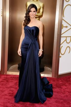 Dark nails might be a Thing. Sandra Bullock has done it, so did Charlize Theron, Emma Watson and Kerry Washington. It works for us. And BTW Bullock looks excellent in McQueen. Navy blue but in a warm way. Nice balance too between the side hair on the left and the pleated detail on the right. IF   Photograph: Steve Granitz/WireImage