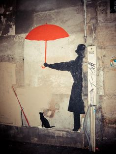 Street art of an umbrella red, a cat kept dry and a man named Fred.