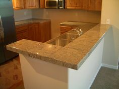 Here are some photos of a countertop and bar that I tiled with 12 x 12 granite  tiles. I