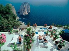 Slim Aarons - Il Canille, Capri, Italy (La Dolce Vita)  Sunbathers lounge on the white-painted terrace of Il Canille, built into the rocks of Pizzolungo overlooking the waters off the coast of the island of Capri, Italy, in August 1980. Il Canille is the villa owned by Italian tailor and fashion designer Umberto Tirelli.
