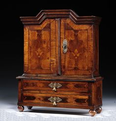 A South German Walnut & Marquetry miniature press cupboard , with a pair of doors opening to reveal shelves above a plinth base with two drawers