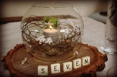 close up of hanging tealight in small fish bowl vase, dodder vine, scrabble table numbers on rustic wood base