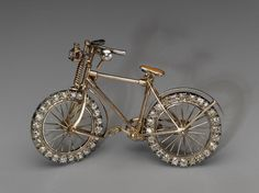 Bicycle brooch        Probably English, mid–1890s      Possibly by Streeter & Co., LTD, English        England  Dimensions      Overall: 4 x 6.5 x 1 cm (1 9/16 x 2 9/16 x 3/8 in.)  Medium or Technique      Gold, enamel, diamond (old brilliant cuts), and ruby