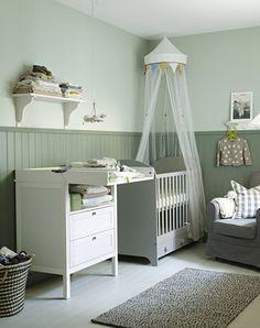 Idées déco chambre bébé : lit bébé à barreaux Gonatt gris perle, 3 tiroirs sous le lit, 2 hauteurs de sommier, ciel de lit en tulle blanc, table à langer commode blancje Sundvik, panier de rangement en osier blanc et noir, étagère murale blanche, fauteuil, tapis blanc et noir - Ikea