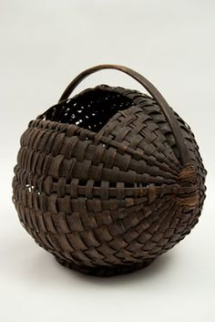 Antique American Chestunut Gathering Basket - Circa 1880-1900: This extremely rare chestnut gathering basket is the most interesting unusual example of early American basketry we have yet to offer to the buying public. With bentwood handle, footed bottom, round construction, and topside opening, this basket was meant to use in the woods and could hold a fine haul of chestnuts.