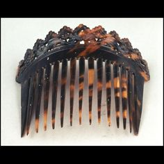 """Woman's ornamental hair comb  ca. 1835 Origin: England or America OL: 5 1/2"" OW: 7"" Tortoise Gift of Tasha Tudor. Acc. No. 1998-244 Woman's decorative hair comb of dark variegated tortoiseshell ornamented with open work carving at top of comb. 15 tapered teeth. Comb is curved to fit a hair bun worn on the crown of the head. Provenance: From the collection of Tasha Tudor.  Abby Aldrich Rockefeller Folk Art Museum"""