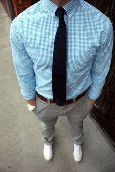 White shoes, gray pants, brown belt, white watch button up long sleeved blue and white shirt and dark blue tie.
