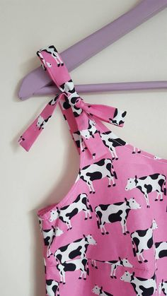 A fun and quirky Cow Print, 100% cotton strap top. Adjust the straps with the bows located at the front to make them shorter or longer. With a vibrant pink backing and Cow Print this top looks beautiful worn with jeans and a cardigan and keeps you cool in warmer weather. This loose fitting top is available in a number of sizes, please see the sizing below. Please contact me with any further questions or if you are unsure about sizing.  Available in sizes:  Small, fitting dress size 10 Bust…