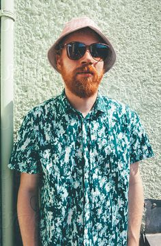 Redheaded man with beard, pink hat and sunglasses by Urs Siedentop & Co