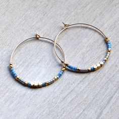 These Blue and Gold 30mm Hoop Earrings were created by hand in London.The earrings are a noticable size at 30mm in diameter and are adorned in a very bohemian yet elegant way, using fair trade, faceted, 22 carat gold vermeil beads along with blue glass beads. They can be worn day and night and look fab with floating layers as well as monocrome beige/white. They would make a great gift for any woman who likes to dress to impress - yourself included!The earrings come in a velv...