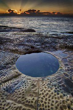 Deep rock hole on the rock shelf north of Curl Curl pool at sunrise. Curl Curl beach, Sydney Australia.