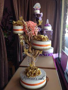 Gold Quinceanera cake on tree stand. Visit us Facebook.com/marissa'scake or www.marissa'scake.com