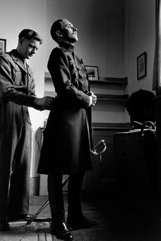 """""""An officer of the elite Queen's Guard being dressed by his aide-de-camp (1952).""""    © Cornell Capa © International Center of Photography/Magnum Photos"""