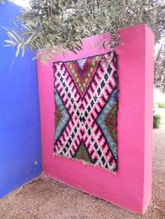 a boucherouite rag rug on the wall in a patio