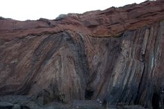 Angular unconformity found on the coast of Portugal at Telheiro Beach. Rock layers that break the sedimentary sequence and contact at noticeably different angles are referred to as an angular unconformity. Here, severely folded schists and metagreywackes of the Brejeira Formation, dating from the Upper Carboniferous are positioned beneath horizontally layered new red sandstones of the Grés de Silves Formation, dating from the Triassic.