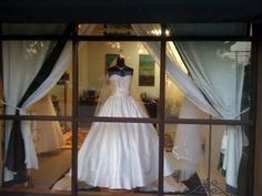 love this window display with a wedding gown framed by curtains